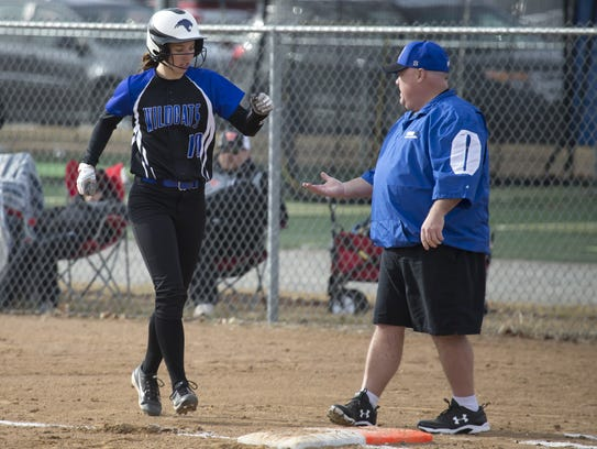 Oshkosh West's Brianna Davis slaps hands with a first-base coach after a base hit in late March.