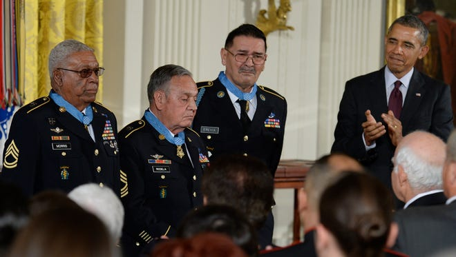 President Obama applauds three Medal of Honor recipients, Sgt. 1st Class (Ret.) Melvin Morris, from left, Master Sgt. (Ret.) Jose Rodela, and Sgt. (Ret.) Santiago Erevia during the White House ceremony March 18.