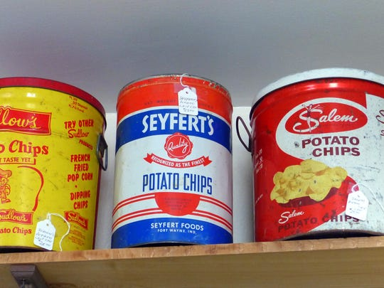 A full shelf of potato chip containers are displayed.