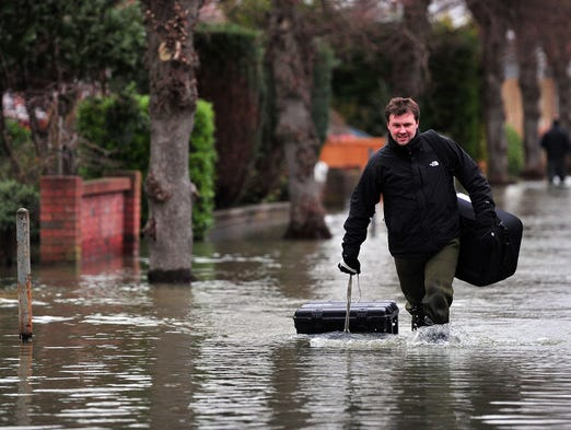 A man drags his possessions in waterproof cases as he wades along a flooded road near Staines, west of London, on Feb. 12. Flooded communities in Britain faced a fresh battering from storms and high winds.