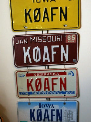 The only license plate number Sam Burrell has ever had and the expired ones hang in his ham radio room Nov. 17 at his home north of Burlington. Burrell got hooked on the radio hobby in 1955 at the age of 14.