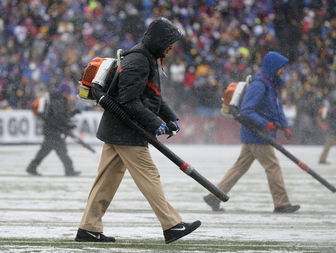 New Era Field staff use blowers to clear snow from