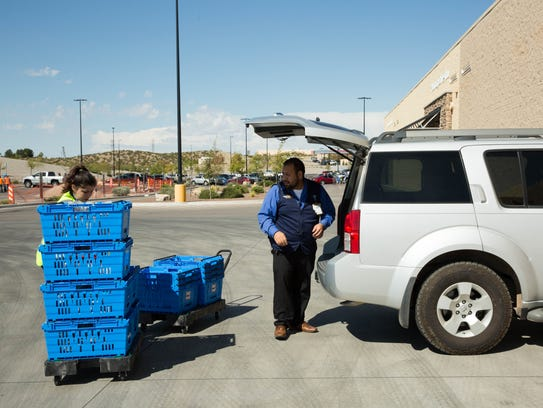 Ray Clark, right, assistant manager for Online Grocery Pickup at the Walmart on Rinconada Boulevard, helps personal shopper April Quezada, left, place groceries into the vehicle of a waiting customer. Thursday October 19, 2017.