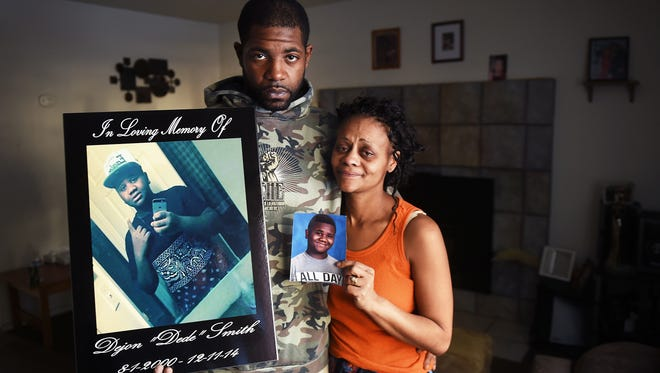 Deshawn, left, and Taneka Smith, parents of Dejon Smith, pose for a portrait with photos of their deceased son in their home in South Lake Tahoe on Dec. 16, 2014.