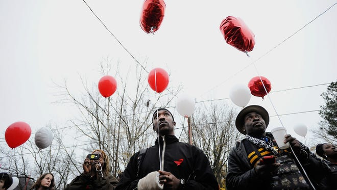 From right, Aubrey Pouncy, Michael Brewer and Brandon Clifton Lee King prepare to release balloons in observance of World AIDS Day on Tuesday, Dec. 1, 2015 in Durham, N.C. (Christine T. Nguyen/The Herald-Sun via AP) MANDATORY CREDIT