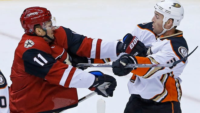 Arizona Coyotes center Martin Hanzal (11) takes a swipe at Anaheim Ducks defenseman Clayton Stoner (3) during the first period of their NHL game Wednesday, Nov. 25 2015 in Glendale.