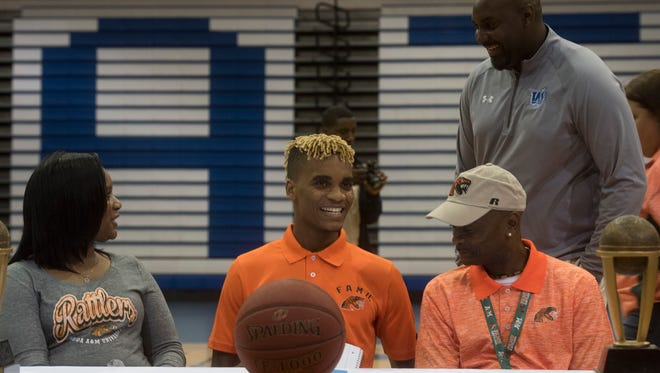 Washington High School basketball standout, Michael Randolph Jr. center, and his parents talk with coach Justin Pierce, standing, before signing with Florida A&M  during a ceremony in the high school gym on Wednesday afternoon.