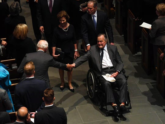 President George H.W. Bush is greeted as he exits the funeral of his wife Barbara Bush.