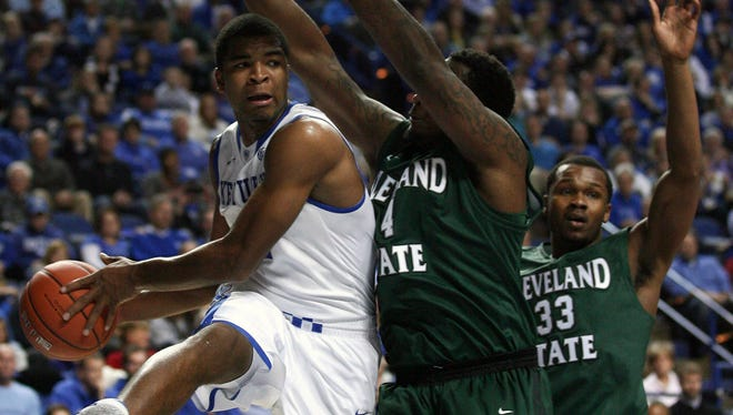Kentucky guard Aaron Harrison (2) looks to pass the ball against Cleveland State center Devon Long (4) and forward Demonte Flannigan (33) in the first half Monday at Rupp Arena.
