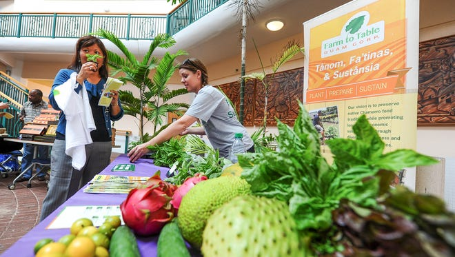 Pamela Peralta, left, Pacific Islands Small Business Development Center associate network director, checks out the fragrance released by a basil plant presented to her by Cassie Brady, Farm to Table Guam Corporation community awareness project assistant, during the Guam One Village One Product event at the University Guam in Mangilao on Friday, Aug. 21, 2015. An introduction of the OVOP program's guidebook and an unveiling of the OVOP product map was held during the event.