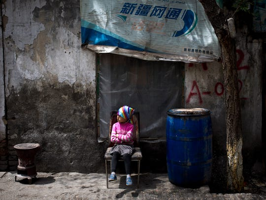 An ethnic Uighur child sits on a broken chair while Uighurs are offering their Friday prayer at a mosque in Urumqi, China's northwestern region of Xinjiang. A day after the attack in Xinjiang's capital of Urumqi, survivors told of their terror during the attack and said they no longer feel insulated from a long-simmering insurgency against Chinese rule, which has struck their city twice in recent weeks.