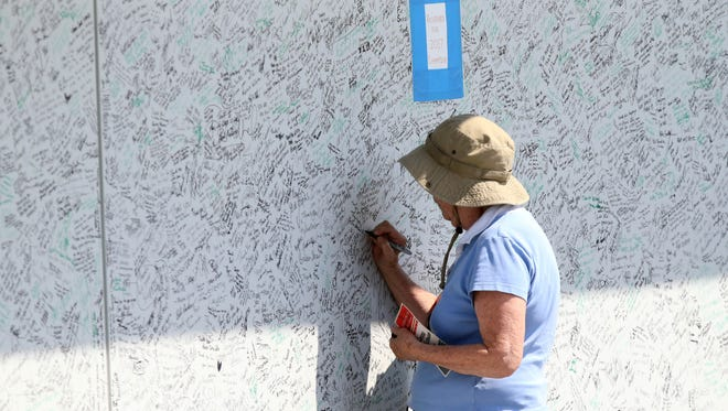 A fan signs the Military Heroes Wall during the final round of the Quicken Loans National golf tournament at TPC Potomac at Avenel Farm.