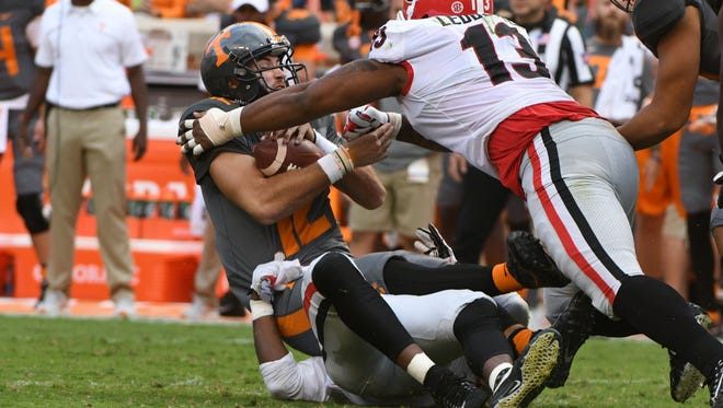 Tennessee quarterback Quinten Dormady (12) is sacked by Georgia defensive end Jonathan Ledbetter (13) and  Georgia linebacker Davin Bellamy (17) during the Tennessee Volunteers vs. Georgia Bulldogs game at Neyland Stadium in Knoxville, Tennessee on Saturday, September 30, 2017.