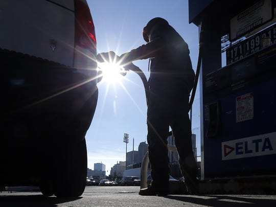 A motorist pumps gas at a Delta gas station in Newark,