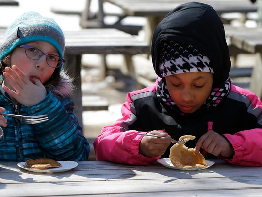 Elise Jacobson (left) and Mia Mays, both members of Girl Scout Troop 8323 from Dunwoody School in Port Washington, enjoy a pancake and fresh maple syrup as they visited Riveredge Nature Center March 10, 2018.