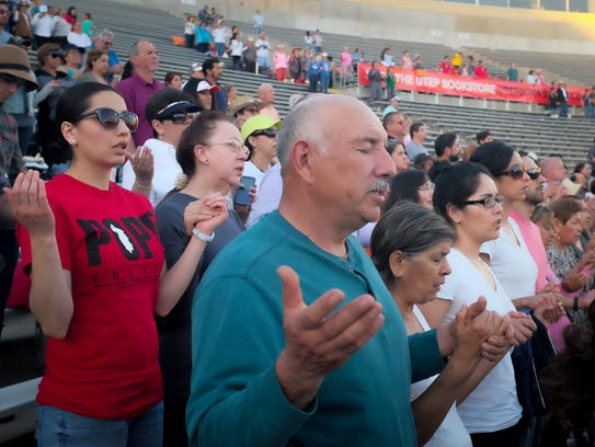 Salvador Quezada lifts his hands in prayer during the