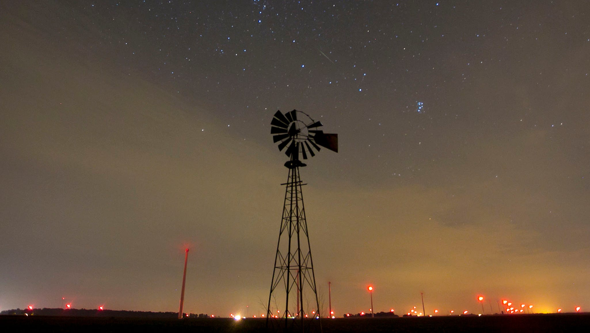 A meteor streaks above an old windmill near Brookston, Ind.