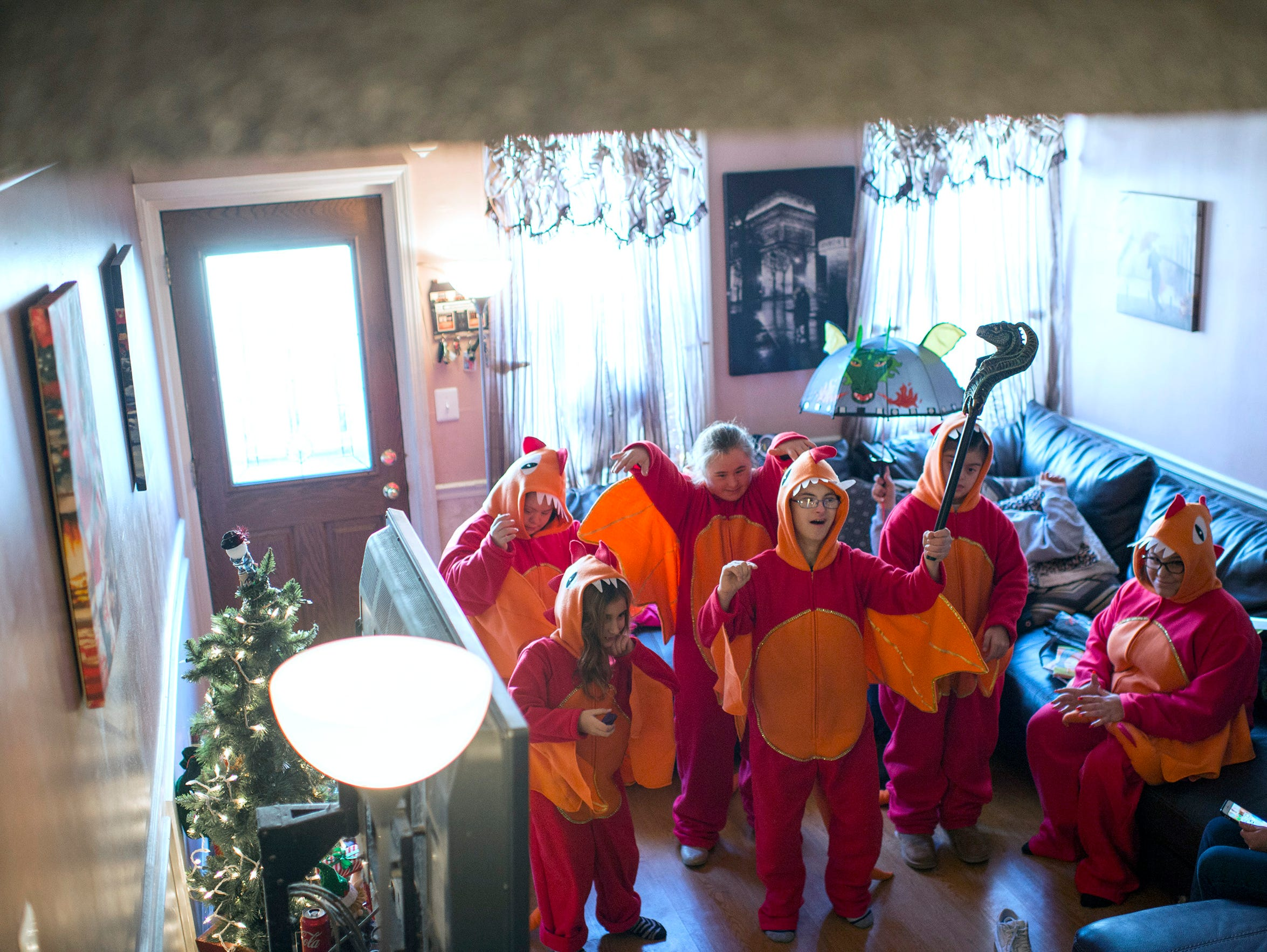 Christopher Sferra, 18, front, leads in a dance as Santino's Dragons try on their dragon-themed Mummers costumes.
