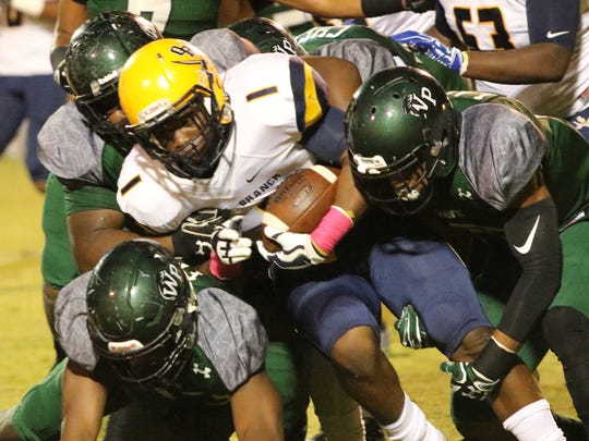 Olive Branch running back Demarcus Ware II (1) is swarmed by West Point defenders during the first half of their Friday night Oct. 13, 2017 football game in West Point, Ms.