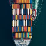 Tugboats help guide a Mediterranean Shipping Co. freighter in this aerial photograph approaching the Port of Long Beach in California in 2013.
