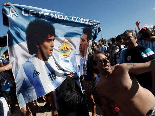 A soccer fan of Argentina poses with a banner of Maradona and Lionel Messi before the start of the final World Cup match between Argentina and Germany, on Copacabana beach in Rio de Janeiro, Brazil, Sunday, July 13, 2014.  (AP Photo/Silvia Izquierdo)