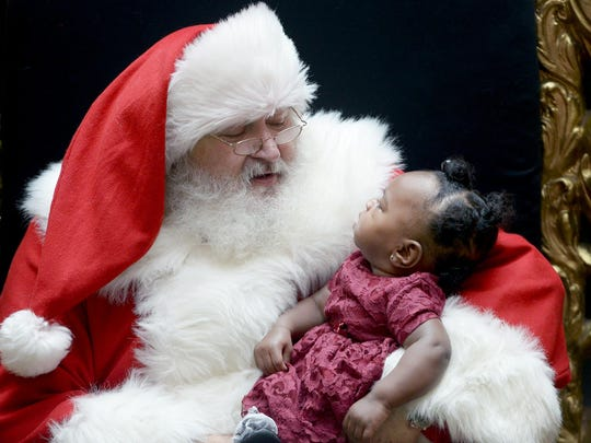 Aniya Cockrell, 6 months old, looks up at Santa before they had their photo taken together at the Old Hickory Mall on Wednesday. Santa has been coming to the mall for nine years.