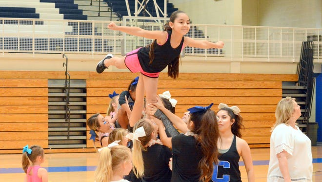 Jolee Munoz, 8, stands on top with one leg during the first annual Carlsbad cheer camp on Wednesday.
