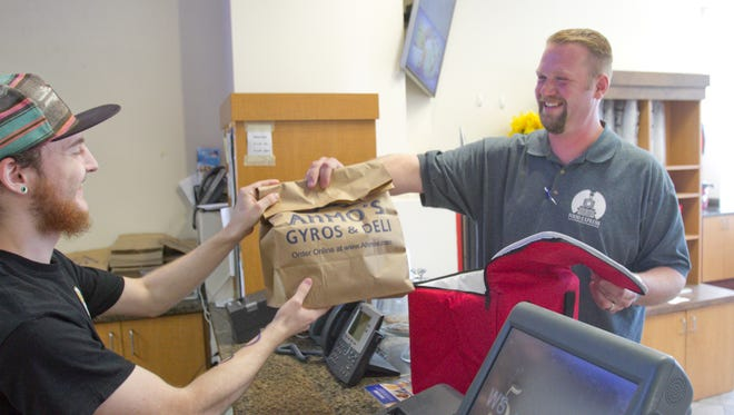 Dennis Graham, right, owner of Brighton Food Express, receives a delivery from Ahmo's Gyros & Deli cook Cas Ora Thursday, July 20, 2017.