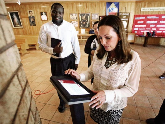 Sofia Larkin Appleby, major gift officer with the Foundation for the Diocese of El Paso, tests a new credit card kiosk installed at St. Raphael Catholic Church at 2301 Zanzibar on Thursday. Watching at left is the Rev. Allan Alaka, parochial vicar at St. Raphael Parish. Diocese officials will test the kiosk to see if it will make tithing for parishioners easier and more convenient.