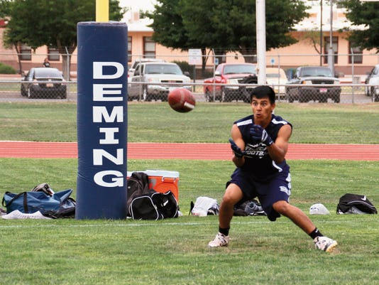 Bill Armendariz - Headlight Photo   Shane Mora is foucsed on an incoming pass in the end zone during a summer 7-on-7 passing drill against the visiting Hot Springs High Tigers, Bayard Cobre High Indians and the Silver High Fighting Colts at DHS Memorial Stadium. The Wildcats open two-a-day practice sessions at 6 a.m. Monday at the DHS practice field.