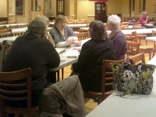 Small groups discuss coordinating efforts to help refugees at the end of Wednesday's meeting.