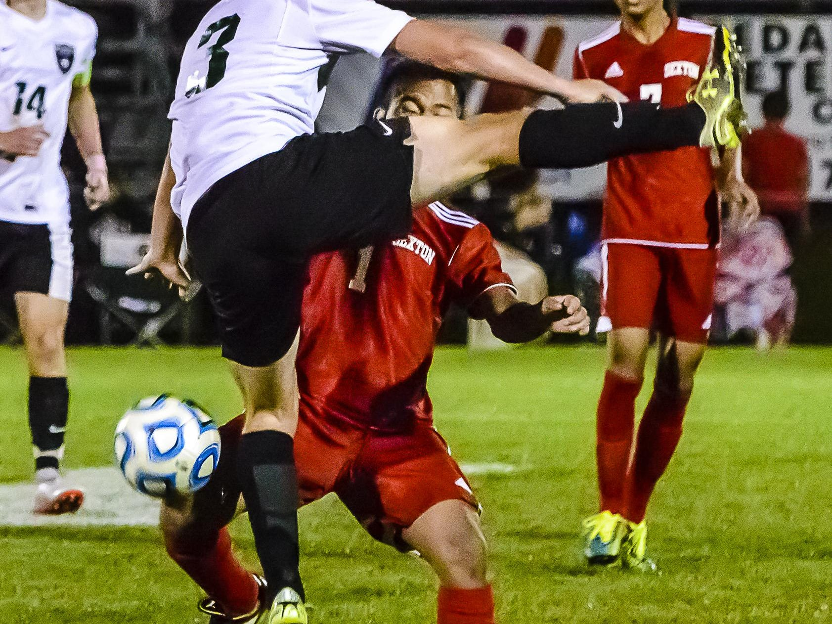 Nang Tuang ,right, of Sexton gets under Alex Scott of Williamston as Scott attempts to head the ball during their Division 3 District Semifinal game Wednesday. Scott would crash to the ground and Tuang would receive a yellow card.