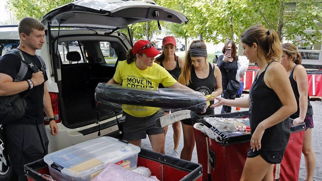 Move-in assistants load bins with student belongings at Ohio State University's Smith-Steeb Hall during early move-in day in 2018. That will not be repeated in August, when on-site assistants will direct traffic and answer questions but not help with moving belongings.
