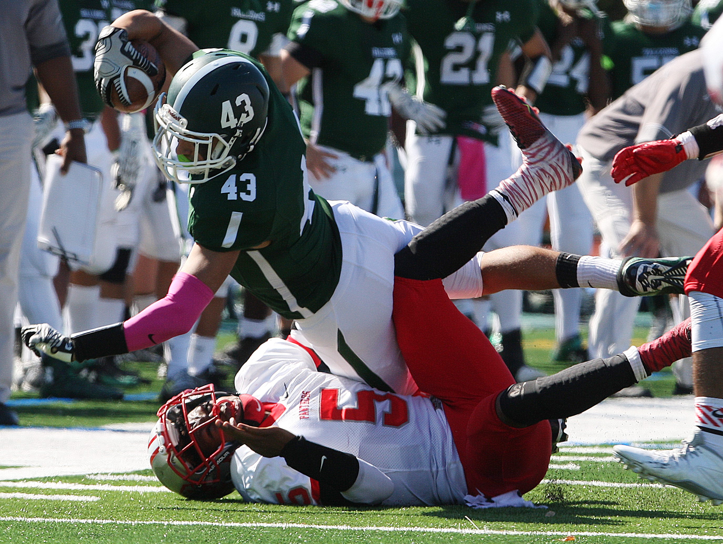 Action photos from the Perth Amboy High School at St. Joseph football game held at St. Joseph's new turf field in Metuhen on Saturday October 10, 2015. Here St. Joseph's # 43 Joe Papa dives over Perth Amboy's # 5 Hakeem Guthrie for 1st down yardage during the first half of play.