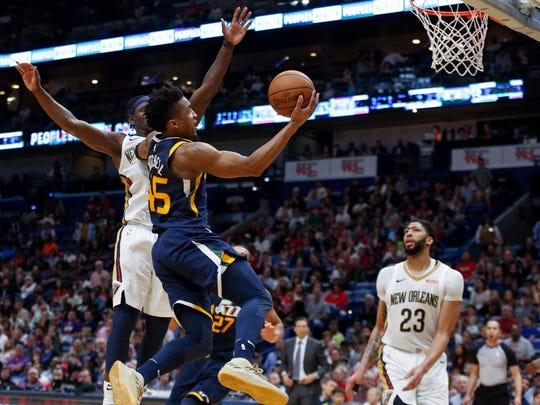 Utah Jazz guard Donovan Mitchell (45) scores against New Orleans Pelicans guard Jrue Holiday (11) in the second half of an NBA basketball game in New Orleans, Sunday, March 11, 2018. (AP Photo/Scott Threlkeld)