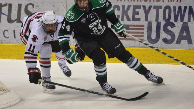 North Dakota's Jordan Schmaltz wins a race to the puck ahead of St. Cloud State's Kalle Kossila (11) on Saturday at the Ralph Engelstad Arena in Grand Forks, N.D.