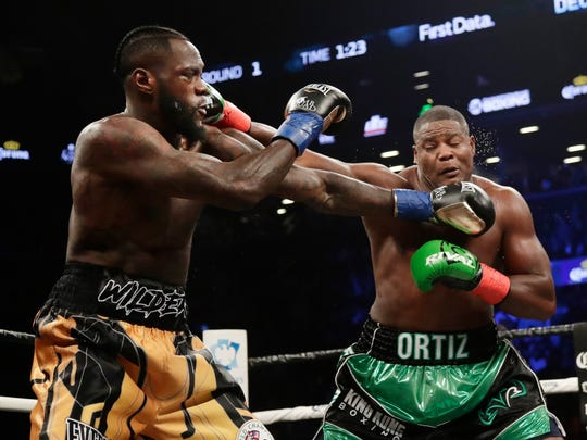 Deontay Wilder, left, and Luis Ortiz trade blows during the first round of the WBC heavyweight championship bout Saturday, March 3, 2018, in New York. Wilder won in the 10th round. (AP Photo/Frank Franklin II)
