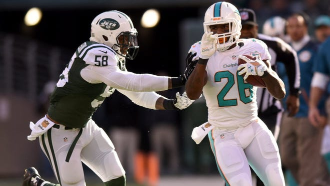 Jets linebacker Erin Henderson pushes Miami Dolphins' Bobby McCain out of bounds during during a November 2015 game at MetLife Stadium.