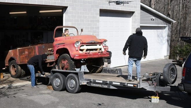Members of the Museum of Off Road Adventure load a 1956 Chevrolet NAPCO fire truck.