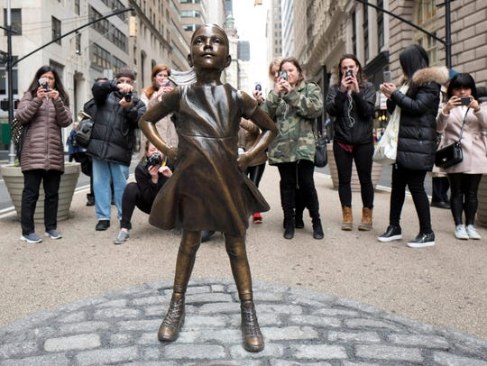 "A crowd gathers behind a statue titled ""Fearless Girl"""