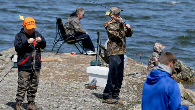 A group of kids with supervising adults fish at Lake Arthur in Moraine State Park in  Pennsylvania. North Jersey offers similar mentoring programs.