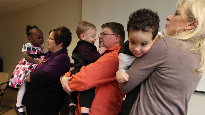 April DeBoer of Hazel Park, Mich., holds her daughter Ryanne DeBoer-Rowse, 1, as her partner Jayne Rowse holds son Jacob DeBoer-Rowse, 2, and April's mother Wendy DeBoer holds Nolan DeBoer, Rowse, 2, after making a statement during a press conference Monday. Partners DeBoer and Rowse filed a federal lawsuit Monday Jan. 23, 2012, to overturn a state adoption law.