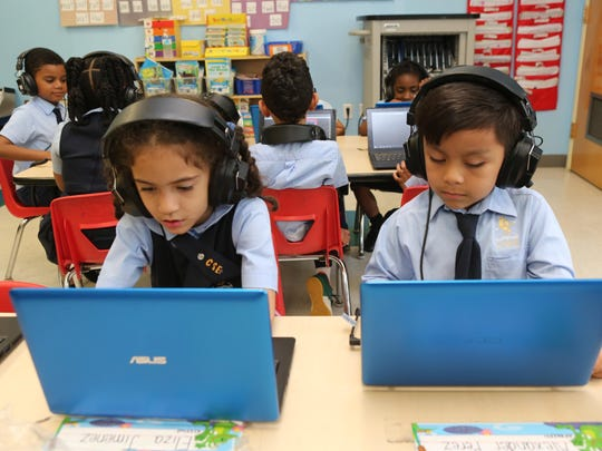 Students Eliza Jiminez and Alexander Perez work with laptops at the Charter School of Educational Excellence in Yonkers.