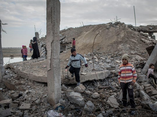 Children play amid rubble on February 16, 2019, in Hajin, Syria. Civilians have begun returning to some small towns close to Bagouz that were recently liberated by the US-led coalition and the Syrian Democratic Forces (SDF). Fighting continues in a small section in the west of Bagouz.