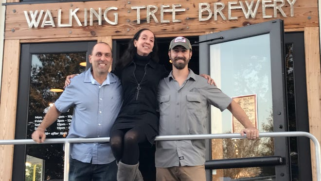 Isaac Perez (left) and Alan Dritenbas (right), owner of Walking Tree Brewery, flank Isaac's partner Yvonne M. Miller before the festivities began.