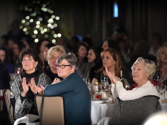 Guests at the ninth annual Neiman Marcus Runway Show applaud fashions on display.