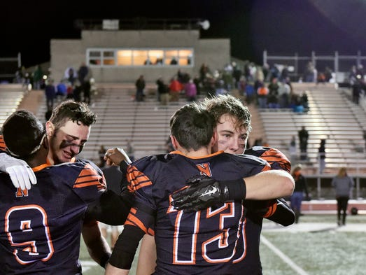 Northeastern football players embrace each other after