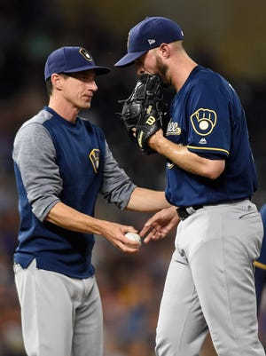 Brewers manager Craig Counsell removes reliever Oliver Drake during Monday night's loss to the Twins in Minneapolis.