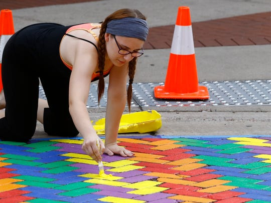 Wausau River District's community arts intern Sarah Lentz, of Wausau, paints a pedestrian cross walk mural in August near the Wausau Center mall entrance. It's the type of pedestrian safety project Allyson Watson had hoped to do in downtown Green Bay.