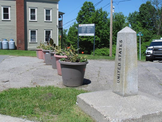 A border post and planters show the U.S. Canadian border